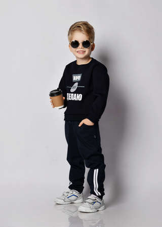 Cool blond kid boy in sunglasses, black sweater with printed words inscription stands holding cap of coffee tea juice drink. Translation: