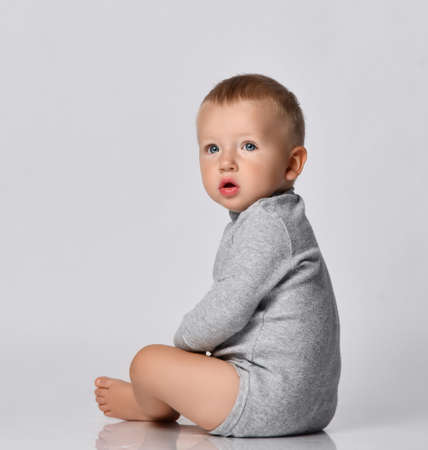 Toddler one-year-old baby boy in diaper and grey one-piece bodysuit with long sleeves sits side and looking to camera with interest. Happy infancy and babyhood concept
