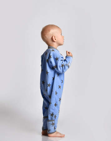 Curious barefooted baby boy in blue fleece jumpsuit with stars stands side to camera looking at upper corner with interest, tries to read, listens carefully holding hand at his opened mouth