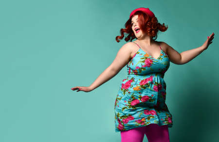Funny overweight fat plus-size woman in hat and colorful clothes jumps high and look at free text copy space on popular mintbackground