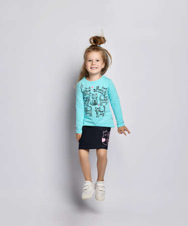 Frolic smiling playful blonde kid girl in stylish shirt and denim skirt with cats kitties and sneakers has fun jumping over gray background. Front view Stok Fotoğraf