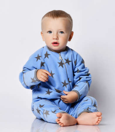 Cute barefooted blond baby boy toddler in blue fleece jumpsuit with stars sits on the floor touching his wearing holding hand up and looks at camera