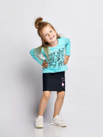 Frolic smiling playful blonde kid girl in stylish shirt and denim skirt with cats kitties and sneakers has fun making faces teases, mocking us over gray background