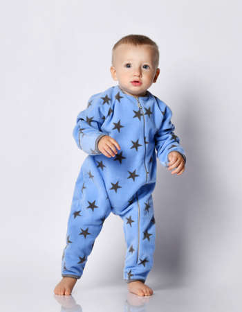 Curious barefooted blond baby boy in blue fleece jumpsuit with stars print pattern stands, going to run, peering out looking at camera