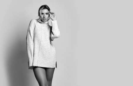 Young sexy beautiful woman in long knitted sweater standing, showing perfect legs and posing over white wall background, copy space. Sexy female look and perfect body concept