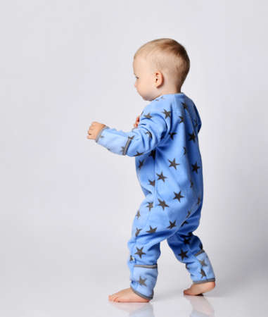 Barefooted blond baby boy toddler in blue fleece jumpsuit with stars stands in fighting stance, walks holding hands up. Side view Stok Fotoğraf