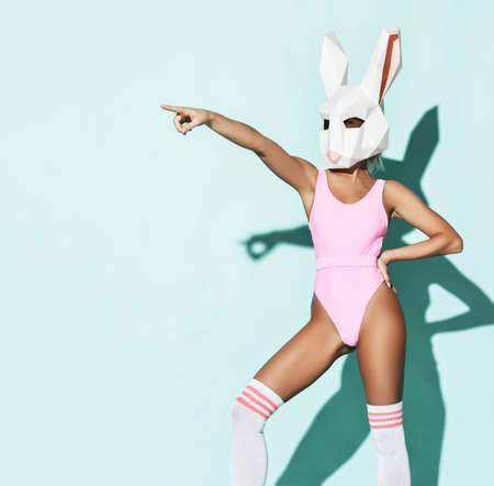 Young sexy fitness slim woman model in pink swimsuit, high socks and decorative rabbit head standing and pointing ahead with finger over blue wall background. Sport and active lifestyle Stok Fotoğraf