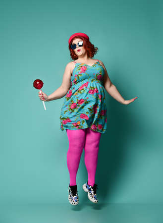 Funny overweight fat chubby woman in funny hat, colorful clothes sundresand tights and with extra big lollipop jumps like she is trying to fly  like a little bird on popular mint background