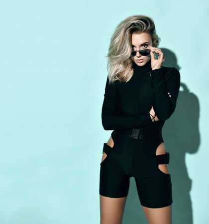 Young blonde slim woman model in black sexy jumpsuit standing and looking at camera over sunglasses over blue wall background, copy space. Sexy female look concept