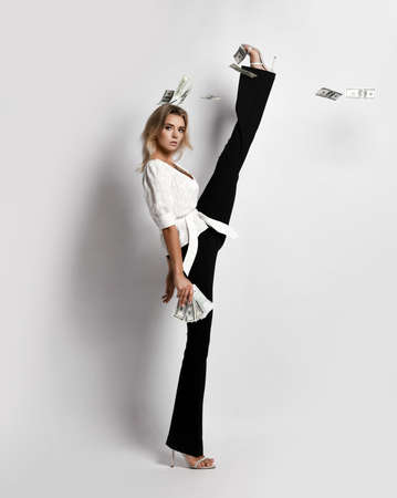 Young sexy blonde slim woman model in shirt and trousers standing in twine with leg raised and holding dollars cash in hand over white wall background. Sexy female look and gymnasts in motion concept