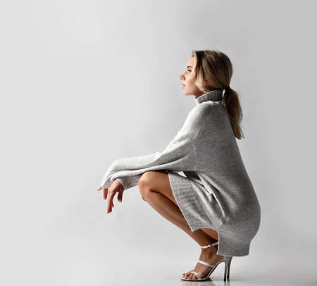 Young sexy beautiful woman in warm knitted sweater and high heels shoes sitting on floor and looking ahead over white wall background, side view. Sexy female look and perfect body concept