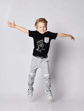 Playful frolic blond kid boy in sunglasses, black t-shirt with dinosaur print and gray pants jumps with hands spread wide, has fun over gray background Stok Fotoğraf