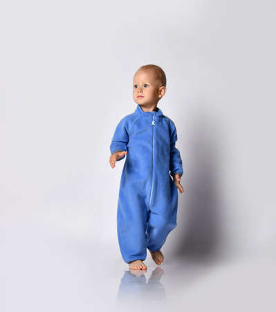 Full-growth portrait of walking going towards camera and looking at upper corner barefooted baby boy in blue fleece jumpsuit with zipper