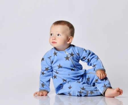 Calm and peaceful barefooted blond baby boy toddler in blue fleece jumpsuit with stars sits on the floor leaning on his arm and looks at copy space at upper corner