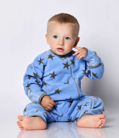 Cute barefooted blond baby boy toddler in blue fleece jumpsuit with stars sits on the floor touching his ear, pointing, scratching, showing where ear is