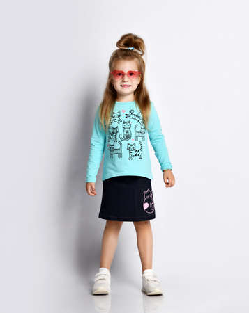 Smiling blonde kid girl in smoked sunglasses stylish shirt and denim skirt with cats kitties and sneakers stands looking at camera over gray background Stok Fotoğraf