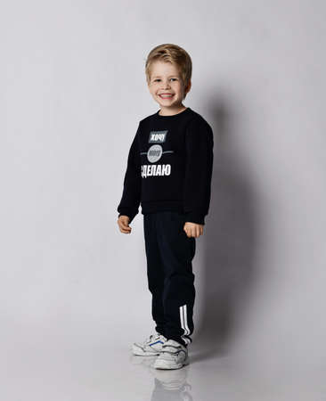 Self-confident cheerful blond kid boy in black jersey sweater with printed words inscription on it  over grey background with copy space. Translation:
