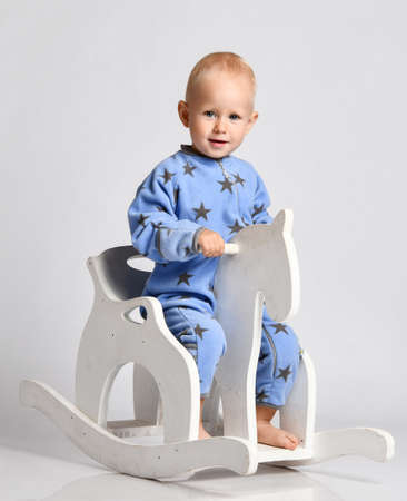 Happy smiling  barefooted baby boy in blue fleece jumpsuit with stars plays rides white kids rocking horse toy and looks at camera Stok Fotoğraf