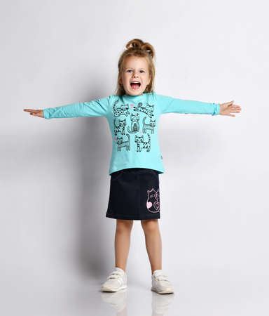 Playful blonde kid girl in stylish shirt and denim skirt with cats kitties and sneakers stands with her arms spread wide and screams loudly over gray background Stok Fotoğraf