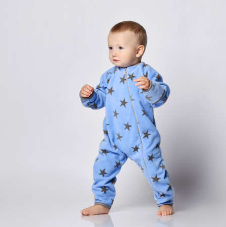 Barefooted blond baby boy toddler in blue fleece jumpsuit with stars stands steadily with his legs spread wide in fighting stance, walks holding hands up and look aside. Front view