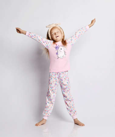 Awakened blonde kid girl in headband, stylish shirt and pants pyjamas with flower print pattern stands and stretches holding hands up over gray background Stok Fotoğraf