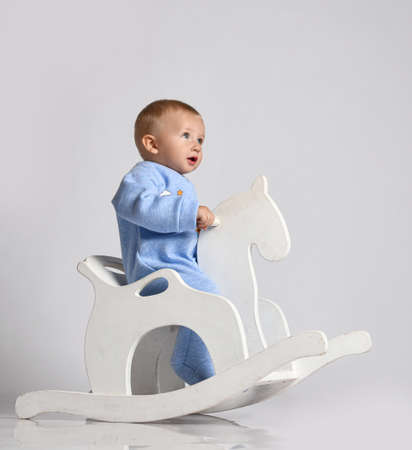 Baby boy toddler in blue fleece jumpsuit overall plays has fun riding white kids rocking horse toy swinging. Side view