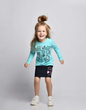 Frolic smiling playful blonde kid girl in stylish shirt and denim skirt with cats kitties and sneakers has fun going to jump, run out over gray background. Front view
