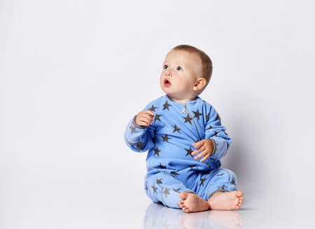 Keen interested barefooted blond baby boy toddler in blue fleece jumpsuit with stars sits on the floor looking with opened mouth at upper corner