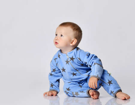 Curious keen barefooted blond baby boy toddler in blue fleece jumpsuit with stars sits on the floor, turn and going to crawl looking at copy space at upper corner Stok Fotoğraf