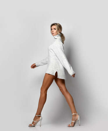 Tall slim long-legged blonde woman in knitted sweater and high-heeled shoes walks passes by camera. Side view. Sexy female look and perfect body concept
