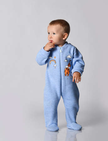 Curious blond baby boy toddler in blue cotton jumpsuit with rainbow and tiger stands holding finger at mouth and looks aside at copy space