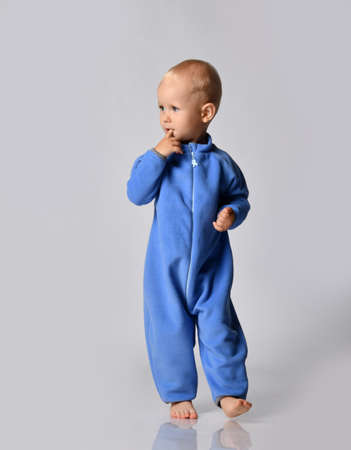 Full-growth portrait of holding forefinger at his mouth walking going towards camera and looking aside barefooted baby boy in blue fleece jumpsuit with zipper