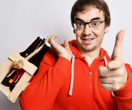 Happy smiling middle-aged man in red hoodie jersey holds a wooden crate with bottles of fresh craft beer drink on his shoulder and points finger at camera. Stylish look for men concept