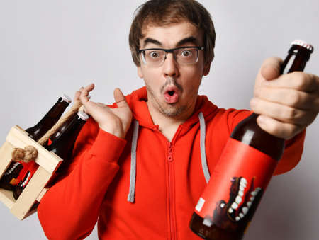 Surprised middle-aged unshaved man in red hoodie jersey holds a wooden crate with bottles of fresh craft beer drink on his shoulder and giving offering us one bottle. Stylish look for men concept