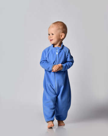 Joyful smiling baby boy in blue fleece jumpsuit walks towards camera holding hand in hand clapping hands looking at free copy space