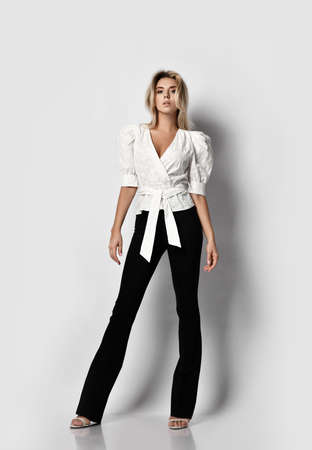 Daring impudent tall blonde slim woman model in office pantsuit shirt with deep neckline and pants stands with legs spread wide. Sexy female look and gymnasts in motion concept