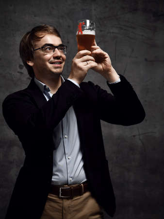 Contentedly smiling middle-aged man in stylish official clothing jacket and shirt holds up a glass of drink craft beer with both hands and looks against light. Stylish look for men concept