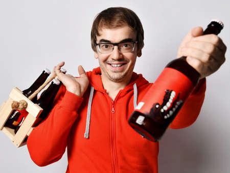 Happy smiling middle-aged man in red hoodie jersey holds a wooden crate with bottles of fresh craft beer drink on his shoulder and giving offering us one bottle. Stylish look for men concept Stock Photo