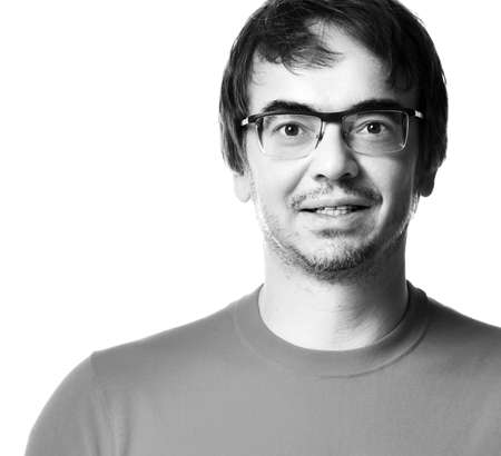 Black and white portrait of excited unshaved man in glasses and t-shirt over white background, close-up. Expressing emotions and moods concept