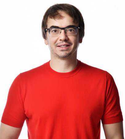 Portrait of smiling positive excited unshaved man in glasses and red t-shirt retelling a story over white background. Expressing emotions and moods concept