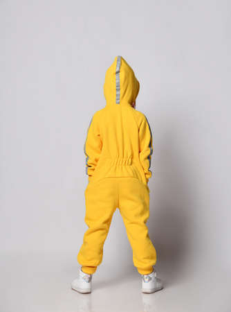 Full-growth portrait kid girl in stylish yellow jumpsuit and sneakers stands back to camera with her hood on and holding hands in pockets over gray background
