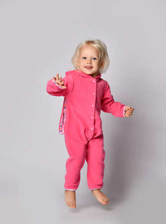 Frolic barefooted curly blonde baby girl in pink warm comfortable jumpsuit jumps looking at camera swinging waving arms. Happy childhood and trendy children wear concept