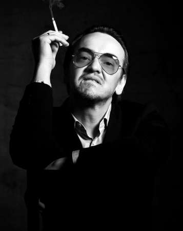 Portrait of brutal rude and impudent man rascal in official clothing and smoked sunglasses smoking cigarette looks down at camera over dark background. Stylish look for men concept