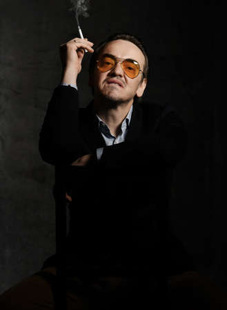 Rude and impudent man scoundrel in formal suit and smoked sunglasses sits on chair backwards smoking cigarette looks down at camera over dark background. Stylish look for men concept