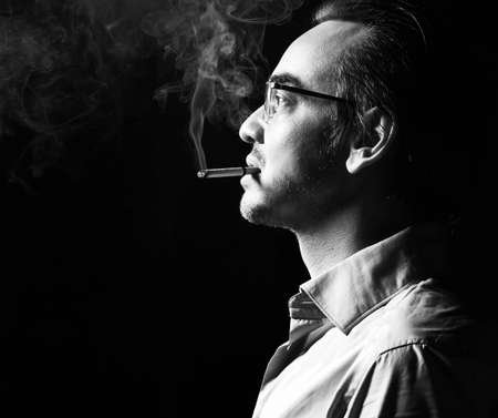 Portrait of brutal strong man business shark in official shirt and glasses stands with cigarette in his mouth, smokes over dark background. Side view. Fashion for men and stylish casual look concept Banque d'images