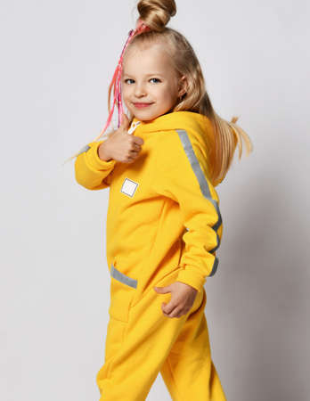 Smiling blonde kid girl with braids in stylish yellow jumpsuit stands back to camera and turned looks at us shows thumb up gestures like sign over gray background