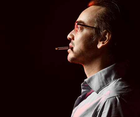 Brutal man business shark in shirt and glasses stands with cigarette in his mouth looking at copy space over dark background. Side view. Fashion for men and stylish casual look concept Banque d'images
