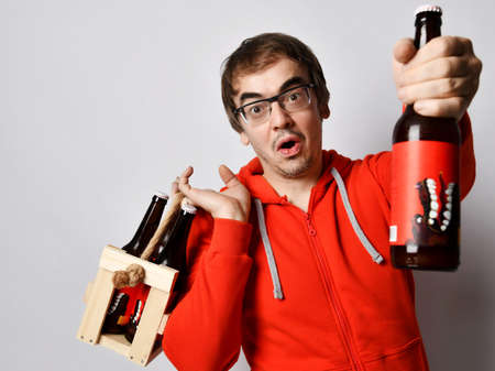 Surprised middle-aged unshaved man in red hoodie jersey holds a wooden crate with bottles of fresh craft beer drink on his shoulder and giving offering us one bottle. Stylish look for men concept Stock Photo