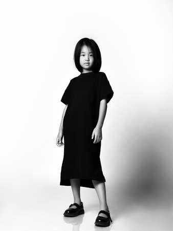 Black and white portrait in profile of self-reliant asian kid girl in black long t-shirt dress, sandals shoes and bob hairstyle standing and looking down at camera