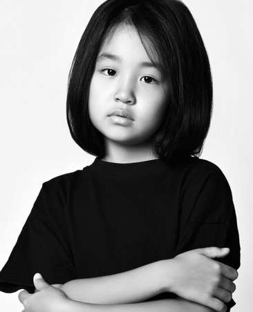 Black and white portrait of asian kid girl in black t-shirt and bob hairstyle standing with her arms crossed at chest and looking at camera with her head tilted